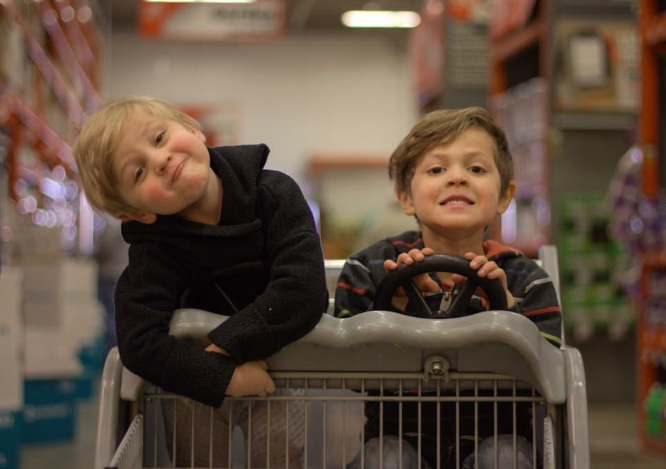 little boys on a shopping cart acting silly