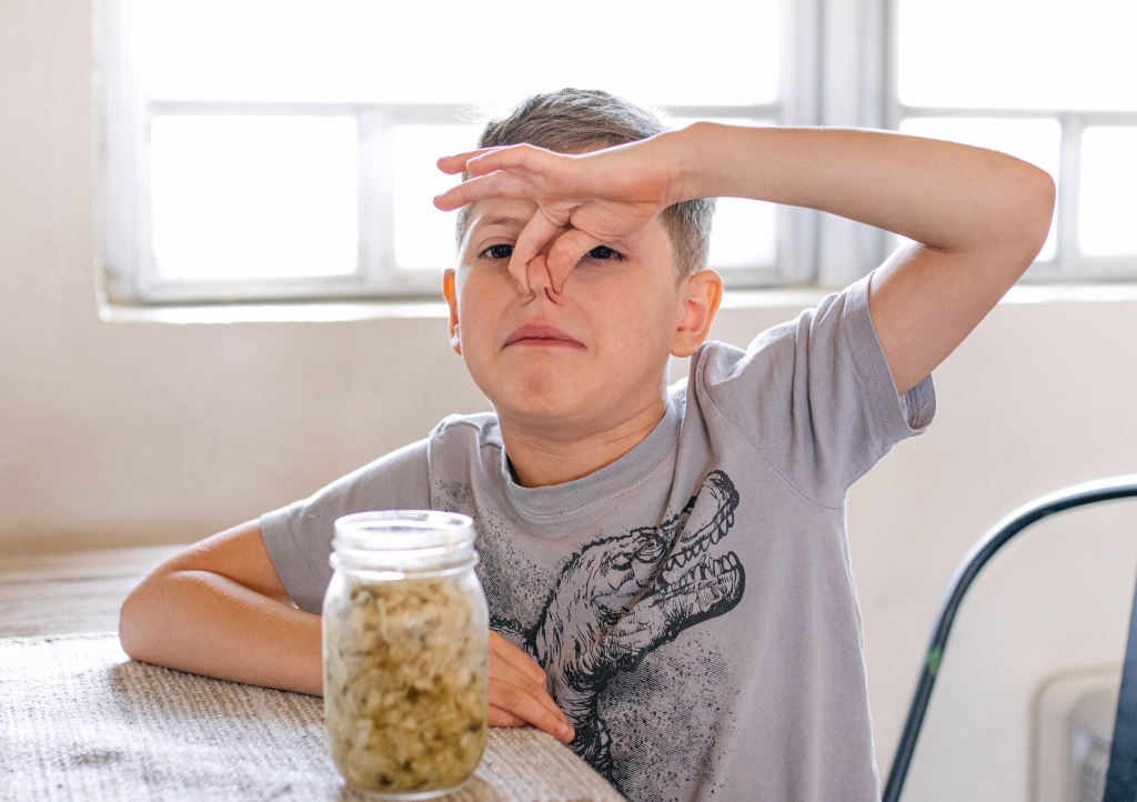 child holding his nose and frowning because he is smelling sauerkraut to complete indoor scavenger hunt