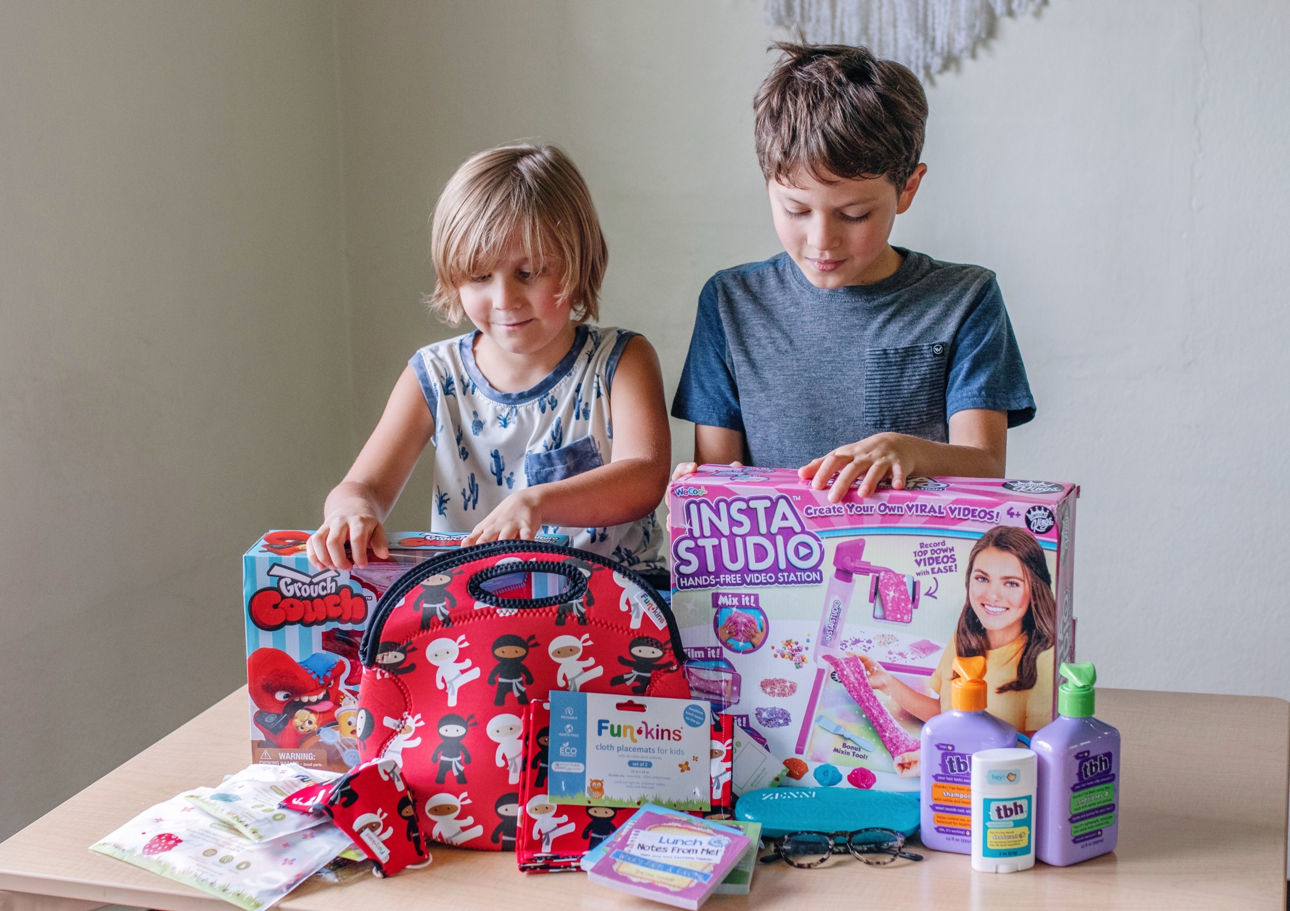 two boys looking at a table full of gifts for back to school